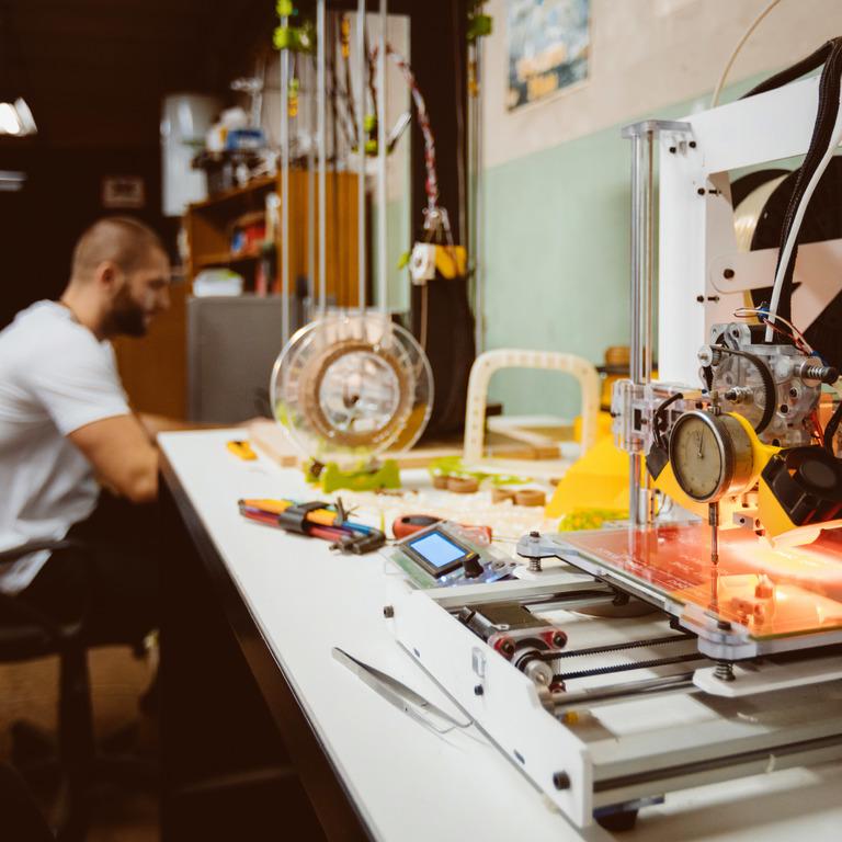 Handwerker sitzt in Werkstatt und arbeitet.