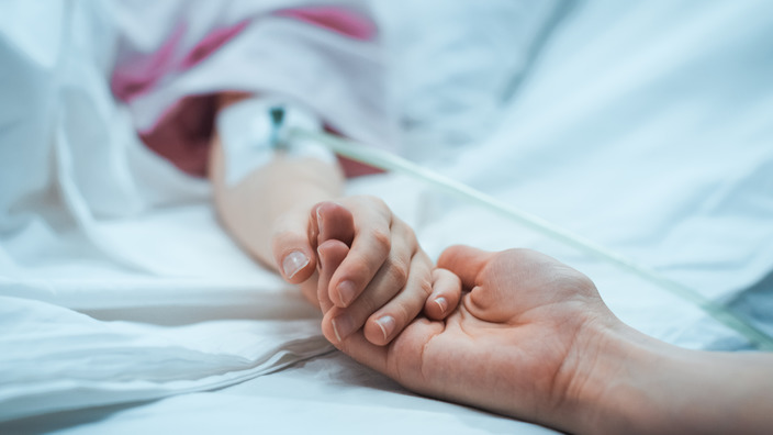 Mutter hält die Hand ihres schwerkranken Kindes
