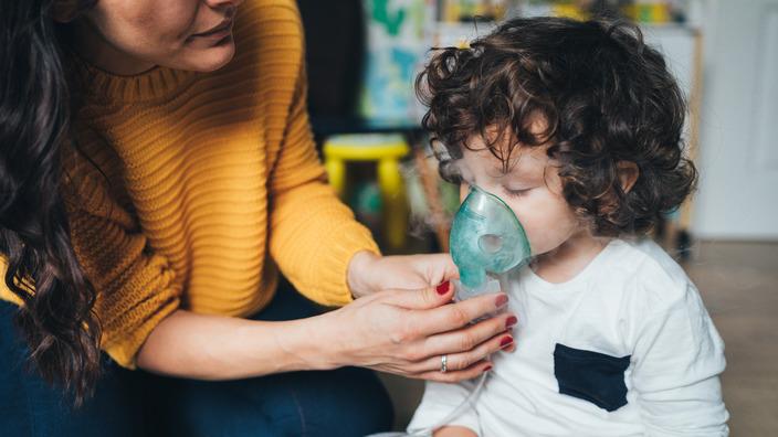 Mutter hilft ihrem kleinen lockigen Sohn mit Mukoviszidose beim Inhalieren