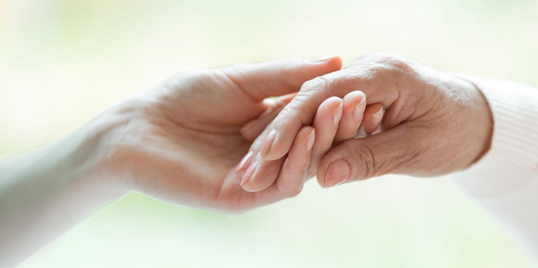 Eine Hand hält die Hand eines Palliativpatienten.