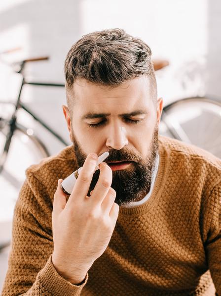 Mann sitzt am Tisch und benutzt Nasenspray