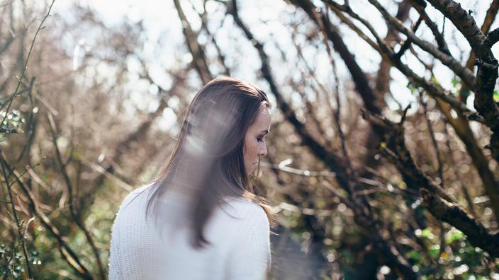Frau steht vor einem entlaubten Baum und schaut traurig