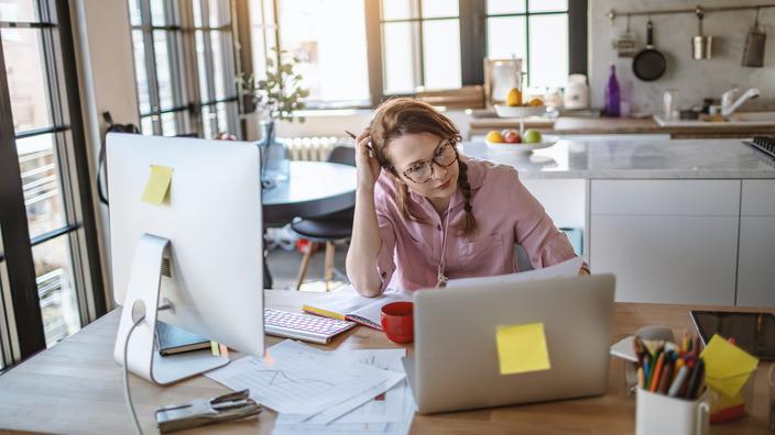 Frau sitzt am Schreibtisch in ihrem Zuhause