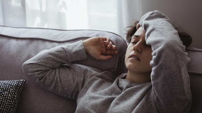 Frau liegt mit Kopfschmerzen auf dem Sofa