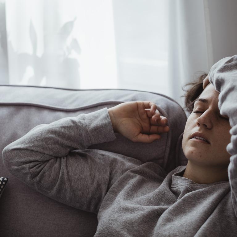 Frau liegt mit geschlossenen Augen auf dem Sofa und hält sich den Kopf