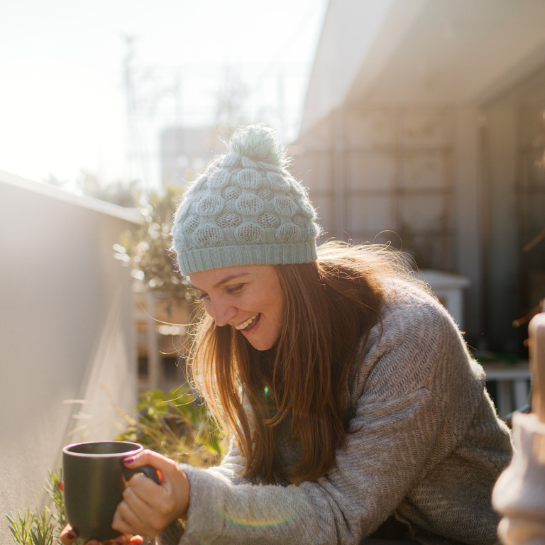Zwei Frauen sitzen im Winter im Garten und trinken Tee.