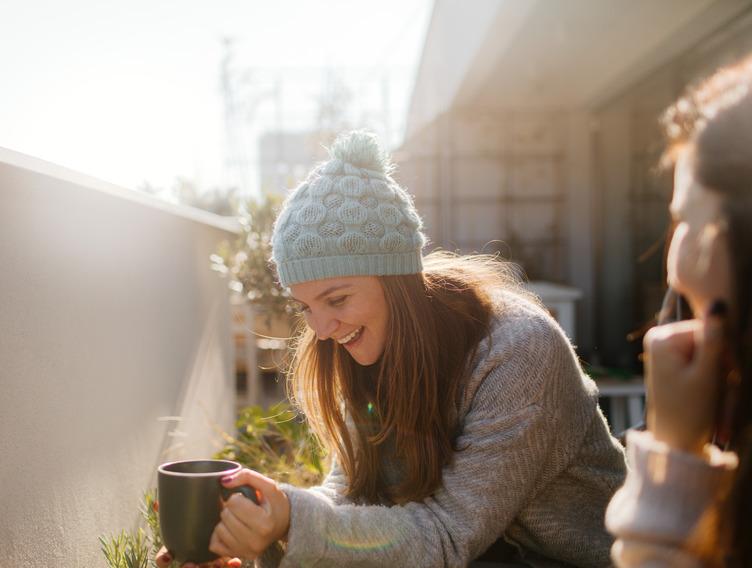 Frau mit Wollmütze sitzt mit Tasse auf dem Balkon in der Sonne.