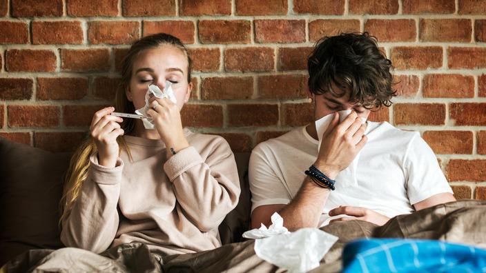 Frau und Mann liegen krank im Bett und schnäuzen in Taschentücher.