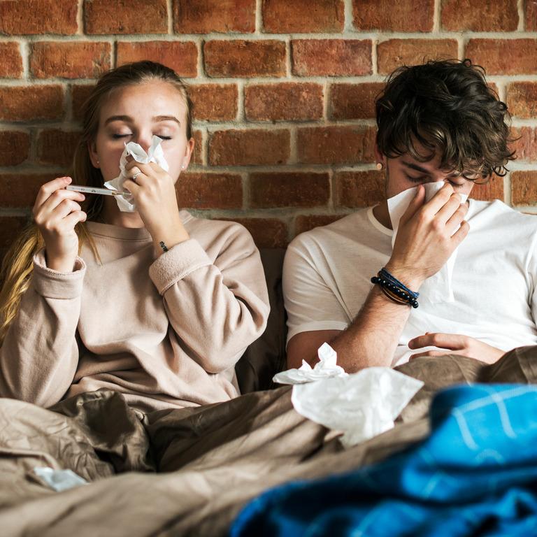 Paar sitzt erkältet im Bett und benutzt Taschentücher