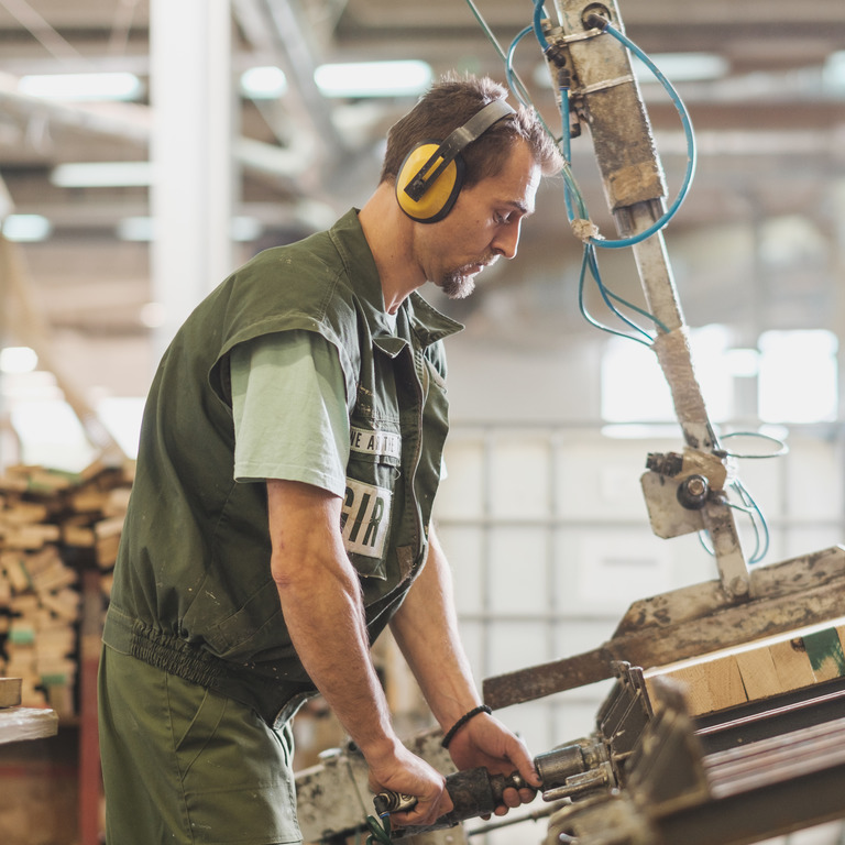 Tischler arbeitet mit Gehörschutz an einer Säge