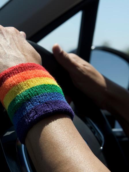 Person mit Armband in Regenbogen-Farben fährt Auto.