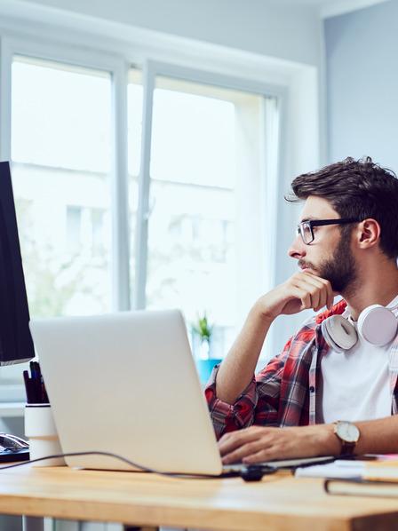 Junger Mann sitzt am Schreibtisch und lernt.