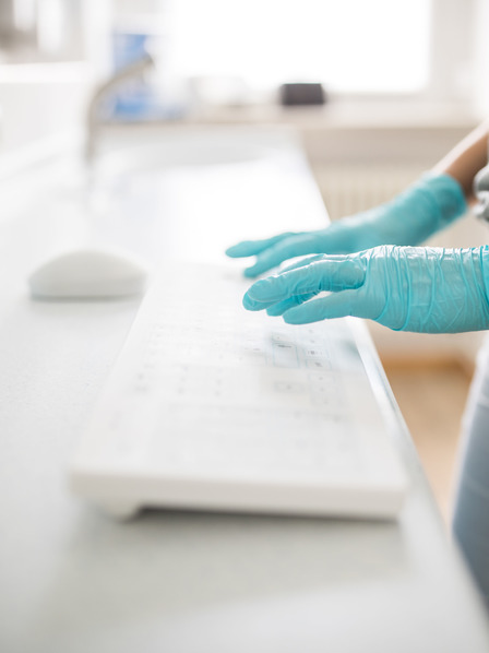 Hände mit medizinischen Handschuhen tippen auf Tastatur