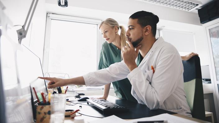 Ärztin und Arzt prüfen etwas am Computer