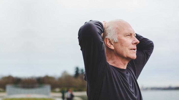 älterer Mann hat die Arme hinter dem Kopf verschränkt und schaut skeptisch