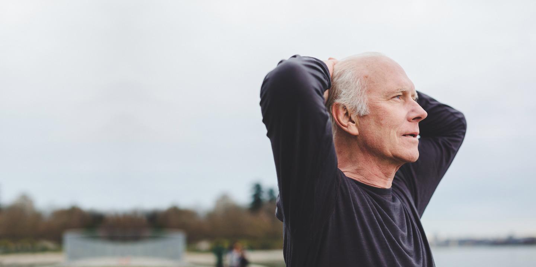 Grauhaariger Mann in Park verschränkt Arme hinter dem Kopf und blickt in die Ferne.