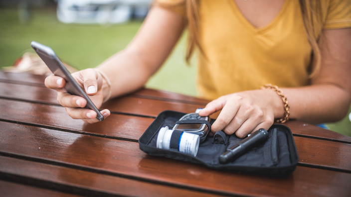 junge DIabetikerin trägt ihre Blutzuckerwerte in eine App ein