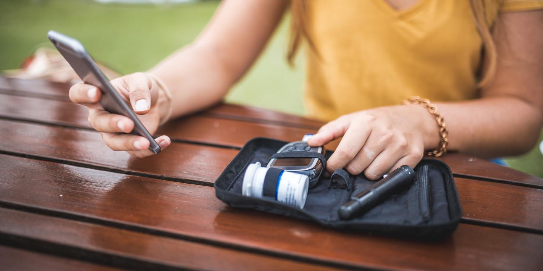 Frau packt mit linker Hand Diabetiker-Tasche aus und in der rechten Hand ein Smartphone.