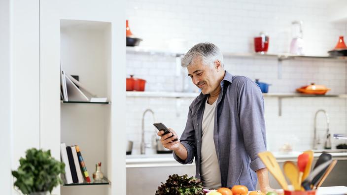 Mann mit DIabetes steht in seiner Küche und checkt Lebensmittel in einer App