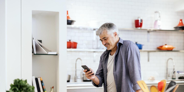 Grauhaariger Mann steht in Küche und hält Smartphone in der Hand.