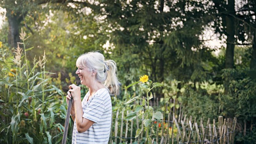 Ältere Frau arbeitet im Garten und lacht.