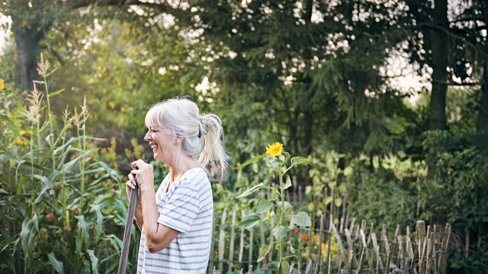 ältere Frau erfreut sich an ihrem Garten