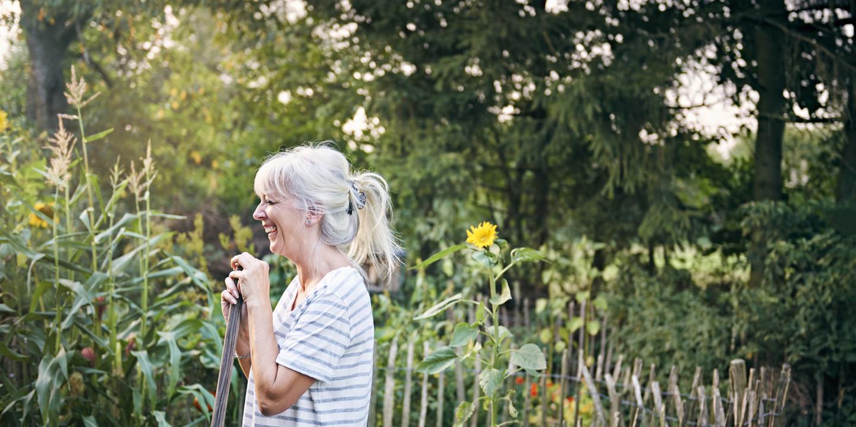 Grauhaarige Frau steht in Garten und hält Schaufel in der Hand.