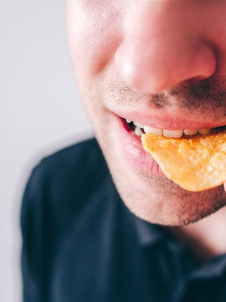 Mann steckt sich Kartoffelchips in den Mund.