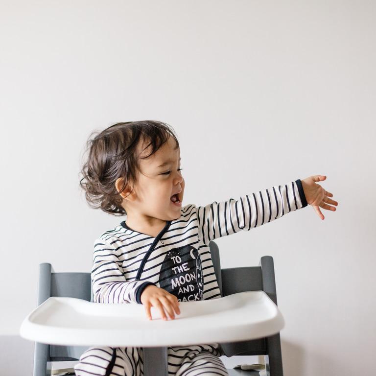 Kleiner Junge sitzt auf einem Hochstuhl und gestikuliert freudig
