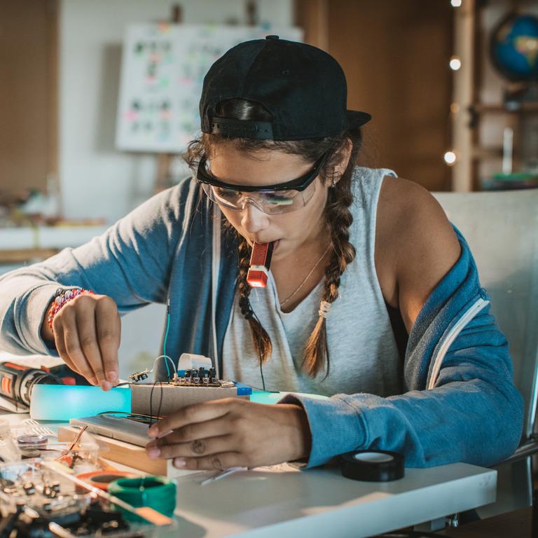 junge Frau arbeitet konzentriert an einem Schaltkreis