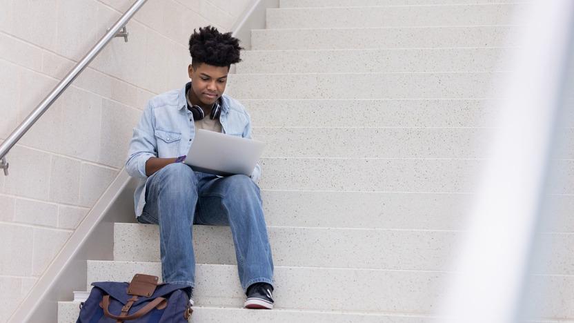 Junge sitzt auf Treppe mit Rucksack und tippt auf Laptop.