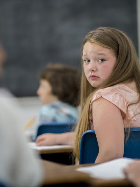 Schülerin die verängstigt ihre Schulkameraden in der Klasse anschaut.