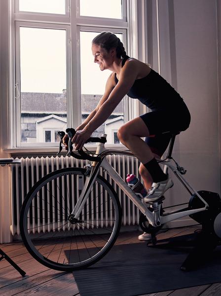 Frau auf einem Fahrrad-Hometrainer Zuhause.