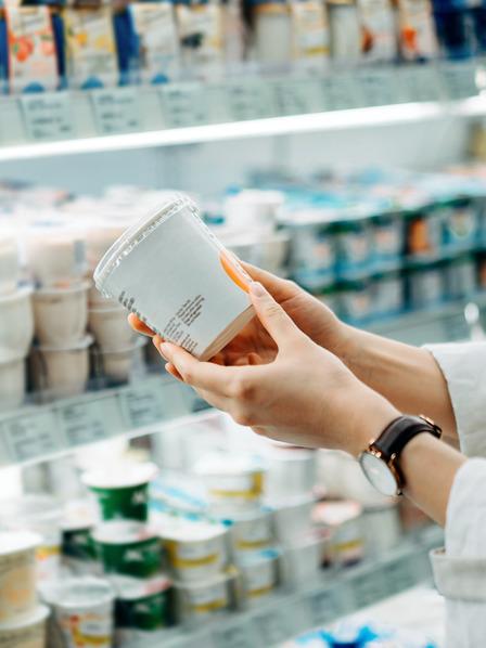 Frau hält ein Pordukt aus dem Kühlregal in der Hand.