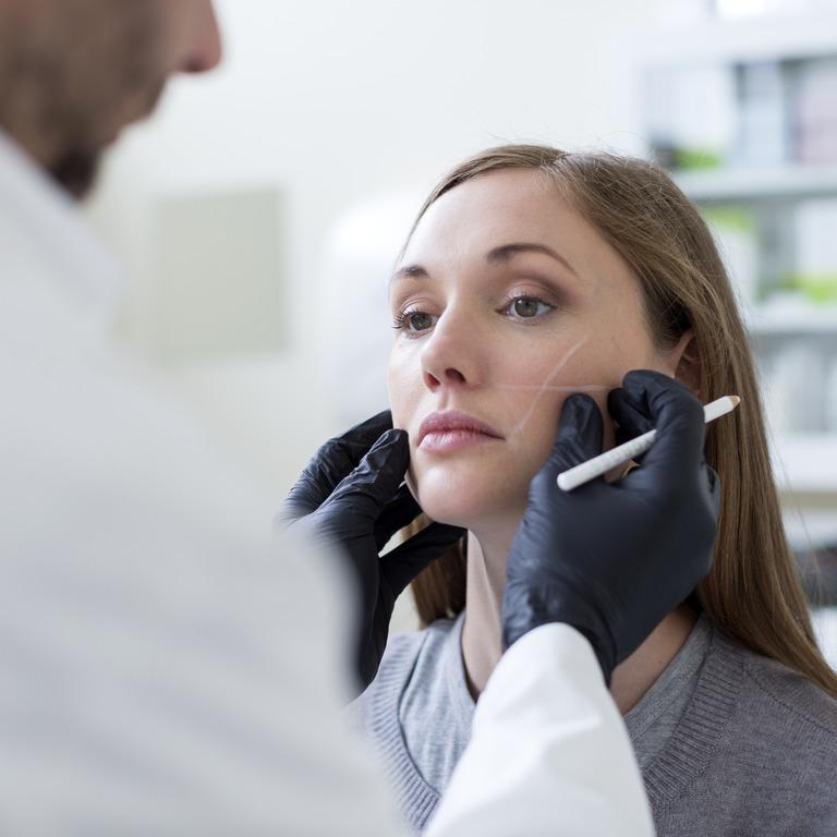 Frau wird von einem Arzt für eine Schönheitsoperation im Gesicht vorbereitet.