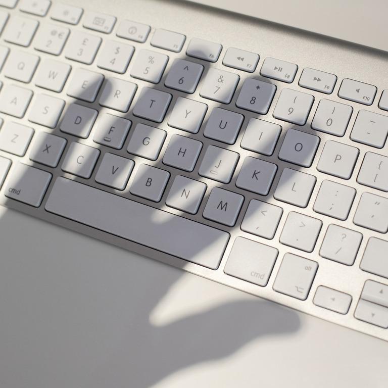Tastatur mit dem Schatten einer Hand darauf