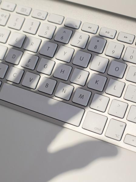 Schatten einer Hand über einer Computertastatur.