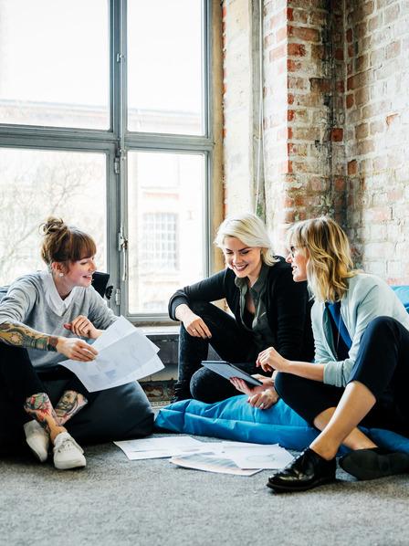 Drei Frauen sitzen im Büro und arbeiten gemeinsam.