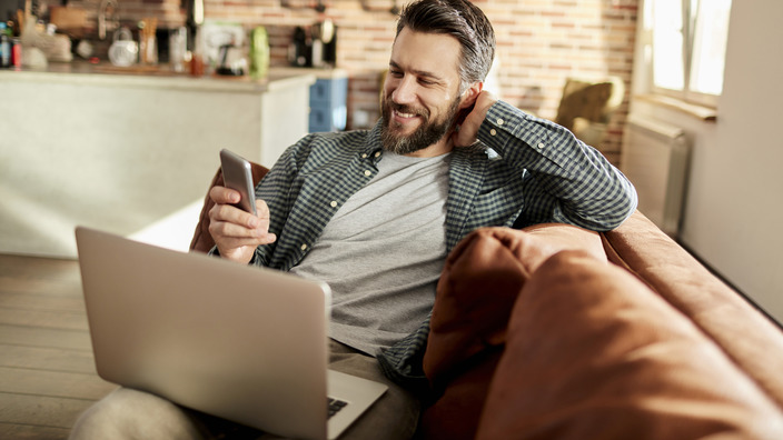 Mann sitzt mit dem Smartphone in der Hand vor dem Laptop.