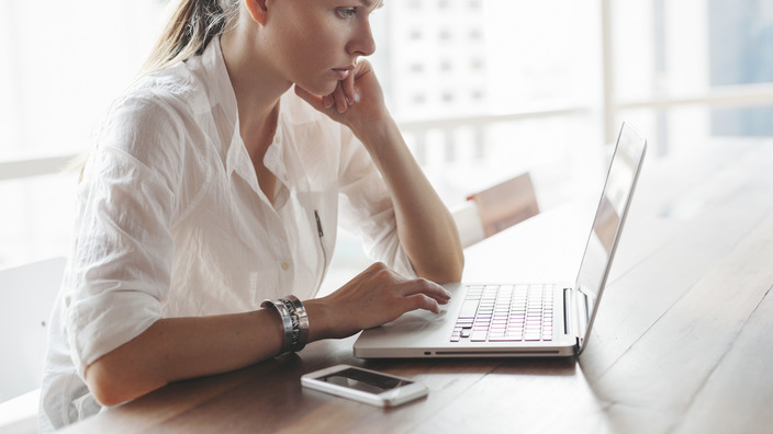 Frau tippt etwas auf ihrem Laptop