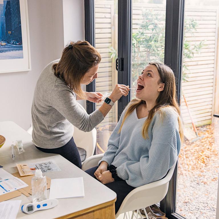Mutter testet ihre Tochter zuhause mit einem Corona-Selbsttest.