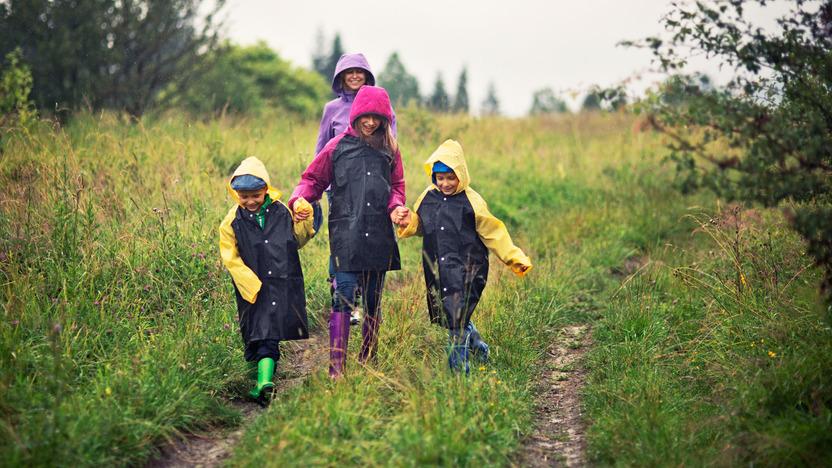 Mutter und drei Kinder spazieren in Regenmänteln auf Feldweg