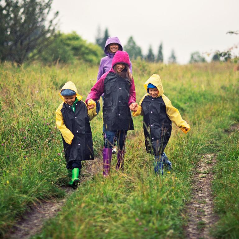 Junge Familie in Regenkleidung geht auf Feldweg spazieren.