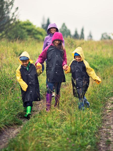 Eine Familie läuft in Regenkleidung durch Wiesen und Felder.