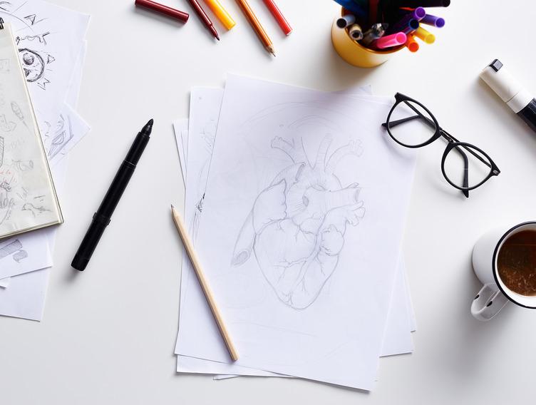 Blatt Papier mit gezeichnetem Herz liegta auf Tisch.