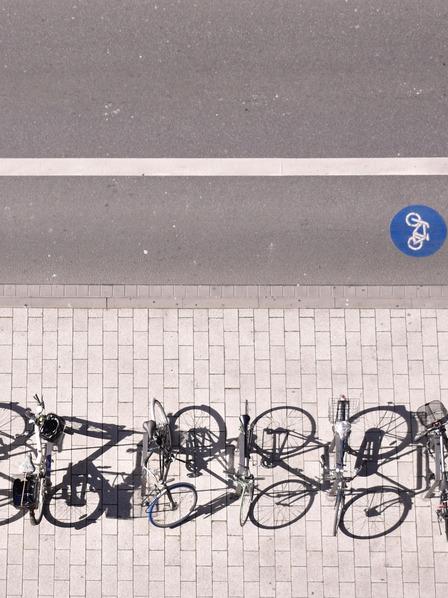 Mehrere Fahrräder stehen geparkt am Straßenrand.