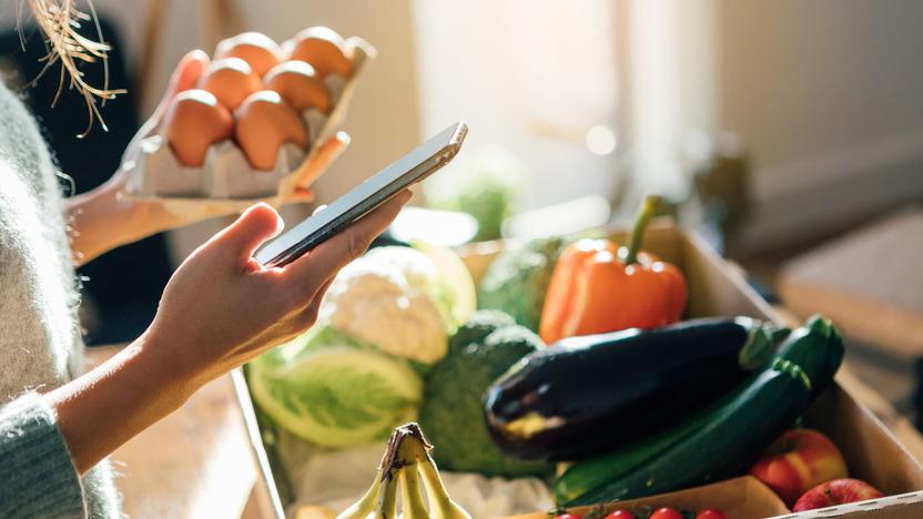 Frau hält Eier und Smartphone in den Händen