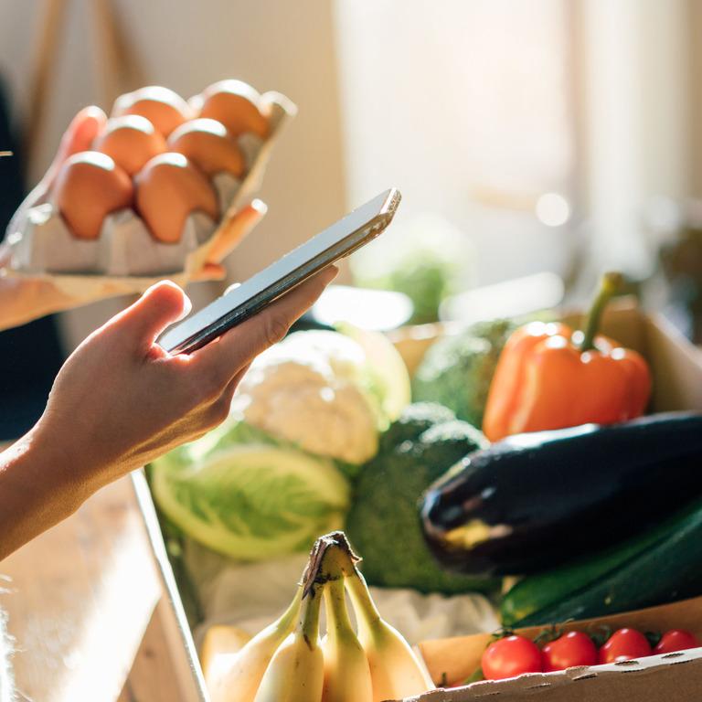 Frau schaut auf ihr Handy und im Hintergrund stehen Lebensmittel