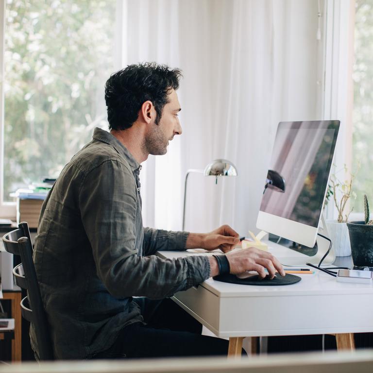 Mann sitzt am Computer Zuhause