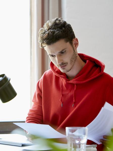 Junger Mann im roten Pullover sitzt am Computer.